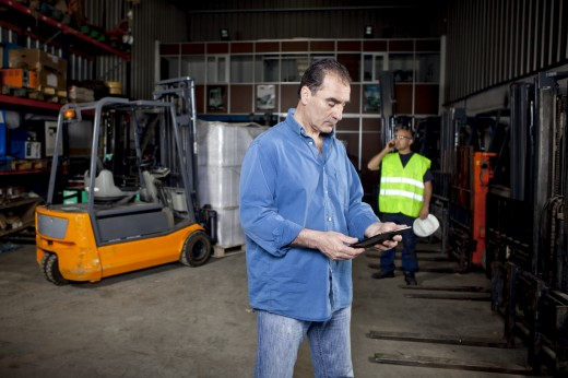 Worker Using Digital Tablet in Warehouse